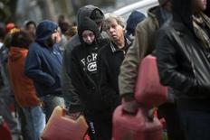 Las víctimas de la supertormenta Sandy en la costa Este de Estados Unidos vieron cómo el frío se sumaba el domingo a problemas como la escasez de combustible y la falta de luz, a solo dos días de unas elecciones que según las encuestas están muy ajustadas entre el presidente Barack Obama y el aspirante republicano Mitt Romney. En la imagen del 3 de noviembre se puede ver una cola de personas soportando el frío para llenar bidones de gasolina en una gasolinera temporal en el municipio de Staten Island, en Nueva York. REUTERS/Keith Bedford