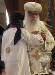 La Iglesia Ortodoxa Copta de Egipto eligió el domingo al obispo Tawadros como nuevo Papa esperando que pueda liderar a los cristianos en un panorama político dominado por el islamismo y que proteja a la mayor comunidad cristiana de Oriente Próximo. En la imagen, un niño con los ojos vendados saca del cuenco el nombre del nuevo Papa copto ante el Papa interino, Bakhomious. REUTERS/Mohamed Abd El Ghany