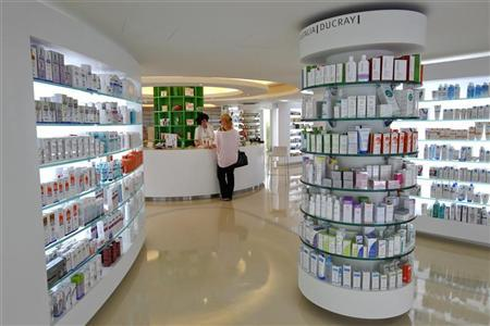 An employee talks with a customer inside a pharmacy in the Glyfada suburb of Athens May 31, 2012. REUTERS/Yiorgos Karahalis