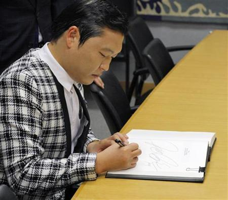 South Korean singer Psy of dance hit ''Gangnam Style'' signs a guest book while he attends a meeting with U.N. Secretary-General Ban Ki-moon during a photo opportunity at the U.N. headquarters in New York October 23, 2012. REUTERS/Eduardo Munoz