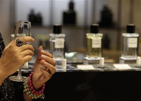 A woman gestures next to a perfume display during a reopening event at the KaDeWe (Kaufhaus des Westens) luxury department shopping store in Berlin September 25, 2012. REUTERS/Tobias Schwarz