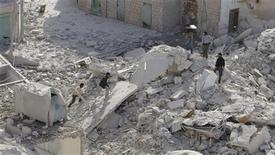Moradores e membros do Exército Sírio Livre caminham sobre escombros de prédio após um avião do Exército Sírio leal a Bashar al-Assad lançar mísseis sobre Taftanaz, perto de Idlib. O Exército sírio bombardeou locais de resistência rebelde no sul de Damasco com artilharia e a partir do ar, horas depois de combatentes da oposição atacarem uma milícia leal ao presidente Bashar al-Assad. 04/11/2012 REUTERS/Abu Qais al-Taftanazi/Shaam News Network/Divulgação