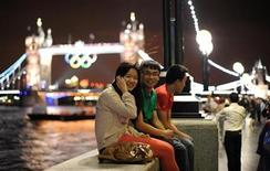 Tourists sit close to Tower Bridge in central London, July 27, 2012. REUTERS/Paul Hackett