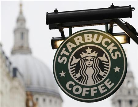 St Paul's Cathedral is pictured behind signage for a Starbucks coffee shop in London October 8, 2012. Picture taken October 8, 2012. REUTERS/Luke Macgregor