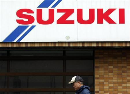 A man walks pasta Suzuki Motor car dealer shop in Tokyo December 9, 2009. REUTERS/Issei Kato/Files