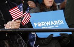 Una donna stringe delle bandierine americane ascoltando il comizio del vicepresidente Joe Biden in Virginia. REUTERS/Kevin Lamarque