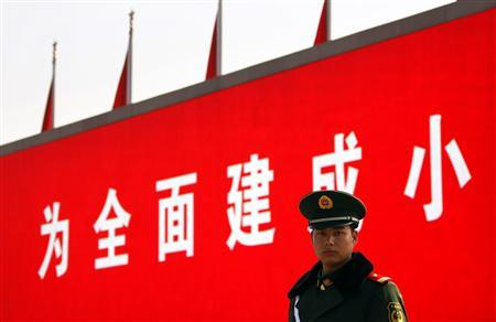 A paramilitary policeman stands guard in front of a screen displaying propaganda slogans on Beijing's Tiananmen Square November 6, 2012 as security is tightened around the square and the adjoining Great Hall of the People. Just days before the party's all-important congress opens, China's stability-obsessed rulers are taking no chances and have combed through a list all possible threats, avian or otherwise. The goal is to ensure an image of harmony as President Hu Jintao prepares to transfer power as party leader to anointed successor Vice President Xi Jinping at the congress, which starts Thursday. REUTERS/David Gray