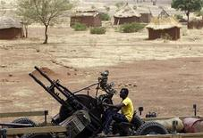 A SPLA-N fighter sits with an anti-aircraft weapon near Jebel Kwo village in the rebel-held territory of the Nuba Mountains in South Kordofan, May 2, 2012. REUTERS/Goran Tomasevic
