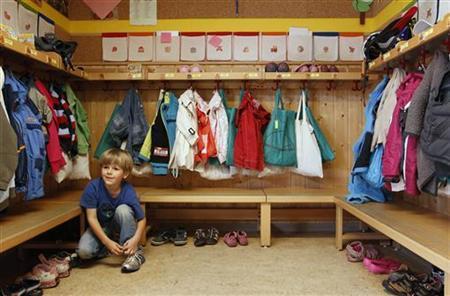 A boy puts on his shoes in a nursery school in Eichenau, near Munich June 18, 2012. REUTERS/Michaela Rehle