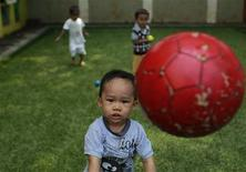 A child plays with ball at Keenkids daycare in Jakarta August 2, 2012. REUTERS/Beawiharta