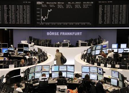 Traders are pictured at their desks in front of the DAX board at the Frankfurt stock exchange November 6, 2012. REUTERS/Remote/Marthe Kiessling
