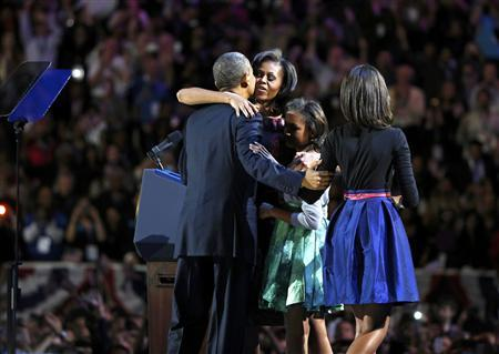 U.S. President Barack Obama is hugged by first lady Michelle Obama and his daughters Sasha and Malia (R) before his victory speech at his election night rally in Chicago, November 7, 2012. REUTERS/Larry Downing