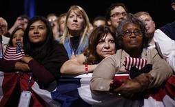 Pessoas escutam discurso de vitória do presidente Barack Obama, em Chicago. 07/11/2012 REUTERS/Jason Reed