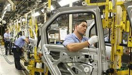 Funcionários trabalham em linha de montagem da fábrica da Renault em São José dos Pinhais. A produção de veículos no Brasil subiu 12,8 por cento em outubro contra setembro, para 318,7 mil unidades, informou a associação que representa as montadoras, Anfavea. 02/08/2012 REUTERS/Rodolfo Buhrer