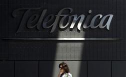 Telefónica dijo el miércoles que no tiene intención de volver a subvencionar los terminales móviles para sus nuevos abonados en España pese a que la eliminación de este incentivo ha reducido la captación de clientes. En la imagen, una mujer pasa junto a la sede de Telefónica en Madrid en una fotografía de archivo de 2010. REUTERS/Susana Vera