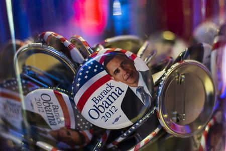 Buttons with portraits of U.S. President Barack Obama lie in a glass bowl during the U.S. election night at the representation of the Bertelsmann media cooperation in Berlin November 6, 2012. REUTERS/Thomas Peter