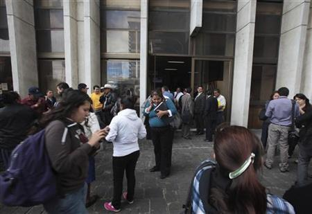 People stand outside the building of the supreme court after an evacuation due to an earthquake, in Guatemala City November 7, 2012. REUTERS/William Gularte
