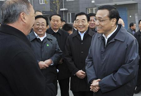 China's Vice-Premier Li Keqiang (R) talks with a resident (L) during his visit to an affordable housing neighbourhood in Langfang, Hebei province, in this November 25, 2011 file picture. REUTERS/China Daily
