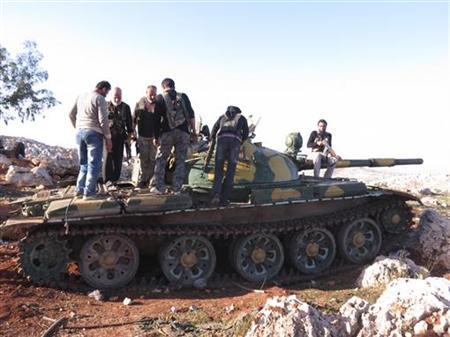 Free Syrian Army fighters stand on a tank after they said they fought and defeated government troops at the air force base at al-Dewala near Idlib November 4, 2012. Picture taken November 4, 2012. REUTERS/Baker Al-Shemali/Shaam News Network/Handout (SYRIA - Tags: POLITICS CONFLICT) FOR EDITORIAL USE ONLY. NOT FOR SALE FOR MARKETING OR ADVERTISING CAMPAIGNS. THIS IMAGE HAS BEEN SUPPLIED BY A THIRD PARTY. IT IS DISTRIBUTED, EXACTLY AS RECEIVED BY REUTERS, AS A SERVICE TO CLIENTS
