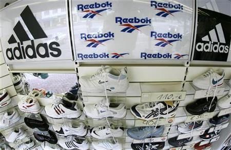 Sport shoes are displayed in a store in the northern German town of Hamburg August 3, 2005. German sporting goods maker Adidas-Salomon is buying U.S. rival Reebok in a 3.1 billion euros ($3.8 billion) deal to expand its reach in Nike's home market.