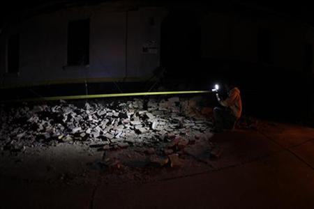A videographer records footage of the damage outside a police station after a 7.4-magnitude earthquake in San Pedro Sacatepequez in the San Marcos region, about 250 km (120 miles) south of Guatemala City November 7, 2012. The earthquake off the coast of Guatemala killed at least 39 people on Wednesday, trapping others under rubble, crushing homes and cars, destroying roads and forcing evacuations as far away as Mexico City. REUTERS/Jorge Dan Lopez (GUATEMALA - Tags: DISASTER ENVIRONMENT)
