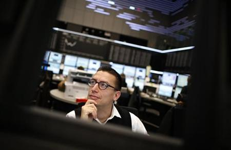 A share trader looks at screens in front of the German share price index DAX board at the German stock exchange in Frankfurt November 7, 2012. REUTERS/Lisi Niesner (GERMANY - Tags: BUSINESS)