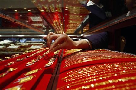 A vendor removes a gold accessory from a glass case at a jewellery shop in Suining, Sichuan province March 29, 2010. REUTERS/Stringer/Files