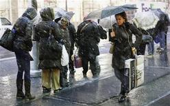 Pessoas esperam em ponto de ônibus durante tempestade de neve no centro financeiro de Nova York. Uma tempestade fora de época no início do inverno provocou neve, chuva e ventanias perigosas na região Nordeste dos EUA, deixando novamente os moradores da região mais populosa do país na escuridão enquanto ainda se recuperam dos estragos causados pela passagem da supertempestade Sandy. 07/11/2012 REUTERS/Brendan McDermid