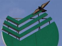 Голубь пролетает мимо логотипа Сбербанка на крыше здания в Санкт-Петербурге, 19 сентября 2012 года. Крупнейший госбанк РФ Сбербанк увеличил чистую прибыль в январе-октябре на 7,6 процента, но снизил чистую процентную маржу, прервав тенденцию опережающего роста розничного портфеля по сравнению с корпоратами. REUTERS/Alexander Demianchuk