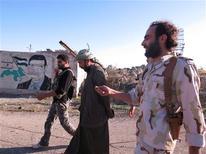El presidente de Siria, Bashar el Asad, ha rechazado toda sugerencia de que pudiera escapar de su país y sostuvo que una eventual intervención extranjera para derrocarlo tendría consecuencias catastróficas para Oriente Próximo. En la imagen, combatientes del Ejército Libre Sirio caminan junto a un cartel del fallecido presidente sirio Hafez al Asad, al que se le ha borrado la cara, tras combates en la fuerza aérea de Al Dewala, cerca de Idlib, el 4 de noviembre de 2012. REUTERS/Baker Al-Shemali/Shaam News Network/Handout ESTA IMAGEN HA SIDO PROPORCIONADA POR UN TERCERO. REUTERS LA DISTRIBUYE, EXACTAMENTE COMO LA RECIBIÓ, COMO UN SERVICIO A SUS CLIENTES.