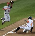 Los Angeles Angels third baseman Maicer Izturis (L) fails to make the out as Baltimore Orioles base runner Adam Jones steals in the fourth inning during their MLB American League baseball game in Baltimore, Maryland, June 26, 2012. REUTERS/Patrick Smith