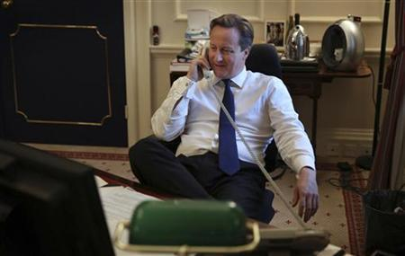 Britain's Prime Minister David Cameron talks to U.S. President Barack Obama on the telephone in his office at 10 Downing Street in London November 8, 2012. Cameron called Obama to congratulate him on his re-election on Thursday. REUTERS/Peter Macdiarmid