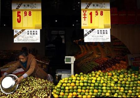 Boards displaying prices hang above a worker as she collects dates for a customer at a food market in central Beijing October 16, 2012. Benign inflation in September showed China has scope to ease policy even as evidence mounts that earlier pro-growth measures are gaining traction, reducing the pressure on policymakers to act as a once-a decade leadership transition approaches. REUTERS/David Gray (CHINA - Tags: SOCIETY BUSINESS FOOD)