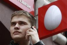"""Человек разговаривает по мобильному телефону у офиса МТС в Москве 5 апреля 2011 года. Российские фондовые индексы продолжили снижение в начале торгов пятницы, но более скромными темпами, а бумаги МТС потеряли в цене больше остальных после сообщения о решении Узбекистана в отношении местной """"дочки"""" оператора. REUTERS/Sergei Karpukhin"""