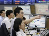 """Валютные дилеры в дилерской комнате банка в Сеуле, 23 сентября 2011 года. Азиатские фондовые рынки снизились в пятницу из-за опасений угрожающего США """"финансового обрыва"""". REUTERS/Lee Jae-Won"""