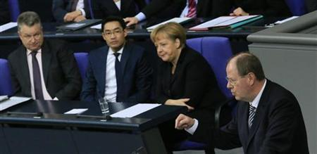 German Chancellor Angela Merkel and Leader of Germany's liberal Free Democrats FDP and Economy Minister Philipp Roesler listen to the speech of Peer Steinbrueck of the opposition Social Democratic Party (SPD) during a session of the lower house of parliament Bundestag in Berlin November 9, 2012. REUTERS/Tobias Schwarz (GERMANY - Tags: POLITICS)