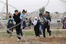 """<p>Un grupo de sirios huyen del pueblo Ras al-Ain rumbo al pueblo turco de Ceylanpinar, nov 9 2012. Alrededor de 11.000 refugiados sirios huyeron hacia tres países vecinos en las últimas 24 horas, el mayor éxodo en """"bastante tiempo"""" en medio del recrudecimiento del conflicto, informó el viernes la agencia de refugiados de Naciones Unidas. REUTERS/Stringer</p>"""