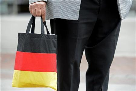 A man carries a shopping bag in the colours of the German national flag in downtown Hanover June 26, 2012. REUTERS/Fabian Bimmer/Files