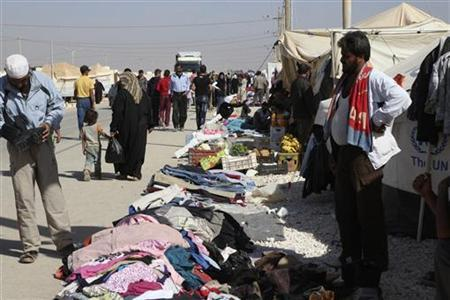 Syrian refugees walk past street vendors displaying goods for sale at the Al Zaatri refugee camp in the Jordanian city of Mafraq, near the border with Syria November 4, 2012. REUTERS/Majed Jaber
