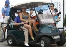 Rory McIlroy of Northern Ireland and girlfriend tennis player Caroline Wozniacki of Denmark ride in a buggy after the rain-delayed second round of the Barclays Singapore Open golf tournament in Sentosa November 10, 2012. REUTERS/Edgar Su