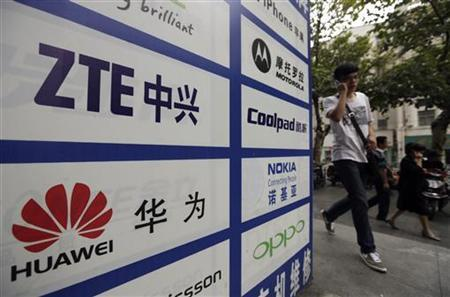 A man walks past an advertisement board showing the logos of Huawei and ZTE on it, outside a mobile phone repair shop in Wuhan October 11, 2012. REUTERS/Stringer/Files