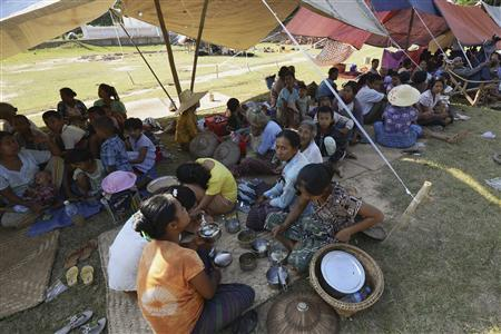 People sit in the shade of a temporary shelter after an earthquake struck their village at Kyauk Myaung township November 11, 2012. REUTERS/Stringer