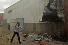 A Palestinian walks near a factory after it was hit by an Israeli tank shell in the northern Gaza Strip November 11, 2012. REUTERS/Ibraheem Abu Mustafa