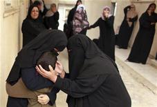 Mulheres palestinas consolam o irmão de Mohammed Hararah, que foi morto em um bombardeio israelense no sábado, durante funeral na Cidade de Gaza. 11/11/2012 REUTERS/Mohammed Salem