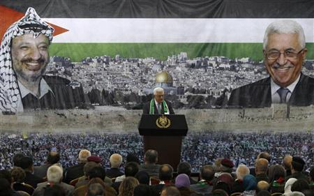Palestinian President Mahmoud Abbas stands in front of a banner with a picture of late Palestinian leader Yasser Arafat (L) during a ceremony marking the eighth anniversary of his death in the West Bank city of Ramallah November 11, 2012. REUTERS/Mohamad Torokman