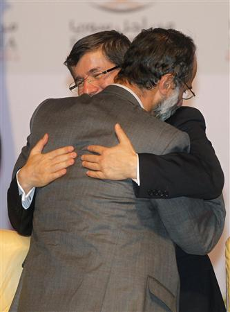 Turkish Foreign Minister Ahmet Davutoglu congratulates new Syrian National Coalition head Moaz al-Khatib during the Meeting of the General Assembly of the Syrian National Council in Doha November 11, 2012. Moaz al-Khatib was elected as the first leader of a new Syrian opposition umbrella group that hopes to win international recognition and prepare for a post-Assad Syria, in a poll counted before reporters on Sunday. REUTERS/Mohammed Dabbous