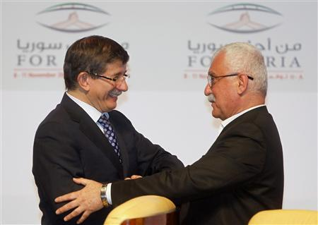 Turkish Foreign Minister Ahmet Davutoglu (L) congratulates new Syrian National Council (SNC) leader George Sabra during the meeting of the general assembly of the Syrian National Council in Doha November 11, 2012. REUTERS/Mohammed Dabbous