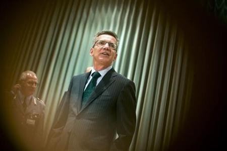 German Defence Minister Thomas de Maiziere is seen through a hole in a chair before a conference of the Bundeswehr leadership in Strausberg near Berlin, October 22, 2012. REUTERS/Thomas Peter (GERMANY - Tags: POLITICS MILITARY)