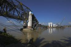 A man sits under the Radana Thinga Bridge over the Irrawaddy River, still under construction, after it collapsed following an earthquake near Singgu Township November 11, 2012. An earthquake struck central Myanmar on Sunday near its second-biggest city, Mandalay, killing at least six people, with the death toll likely to rise as part of an unfinished bridge fell into the Irrawaddy River and several workers were missing. REUTERS/Stringer