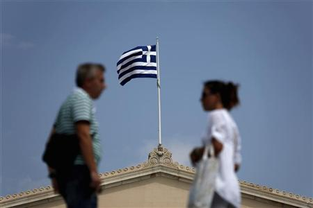 A man and a woman talk as a Greek flag flutters atop the Parliament House in Athens August 13, 2012. REUTERS/Yorgos Karahalis